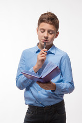 Emotional teenager boy brunette in a blue shirt with a diary and a pen in hand on white background