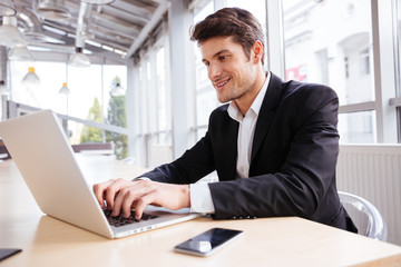 Cheerful businessman using laptop and mobile phone at the table