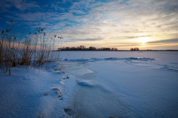 Beautiful winter landscape with frozen lake and sunset sky.
