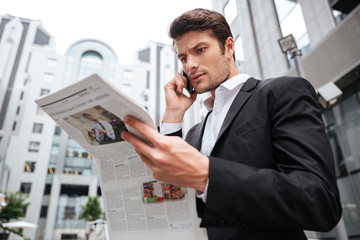 Concentrated young businessman talking on cell phone and reading newspaper