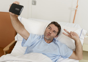 attractive man lying on bed hospital clinic holding mobile phone taking self portrait selfie photo