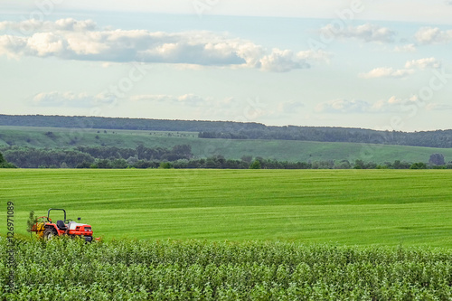 Small red farm tractor on a background of green meadows agricultural background with copy - Small space farming image ...