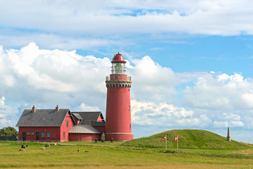 The red Lighthouse Bovbjerg Fyr with green grass and blue sky, J