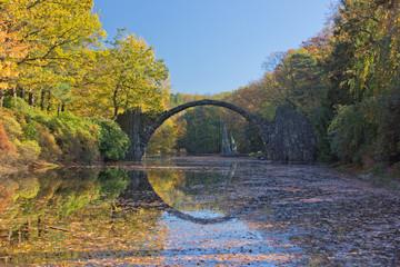 Arch Bridge in Kromlau, Saxony, Germany. Autumn in Park. Rakotz bridge in Kromlau