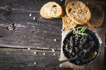 Black Astrakhan Russian salted sturgeon caviar in a can on dark background with wooden spoon and slices of bread. Snacks luxury holidays