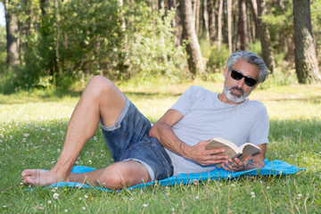man lyingsitting in the grass reading a book
