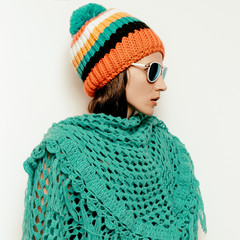 Brunette girl Pom pom hat and knitted scarf. Stylish sunglasses.