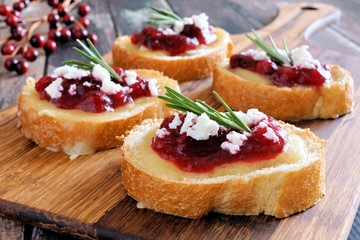 Holiday crostini appetizers with cranberry sauce, brie, feta and rosemary on a wooden server