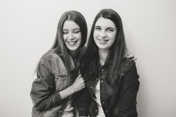Two fashion young women posing in studio