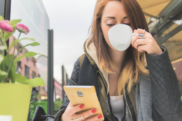Attractive girl using smartphone at restaurant drinking coffe