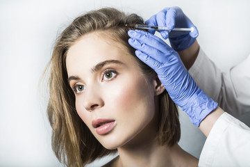 Doctor aesthetician makes head beauty injections to beautiful female patient