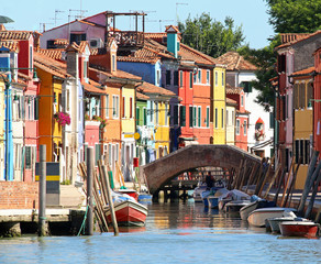 colored houses and a bridge on Canal in Burano island near Venic
