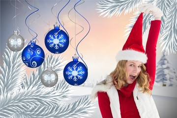 Excited beautiful woman in santa hat against digitally generated