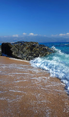 Rocher et écume sur une plage de sable Corse