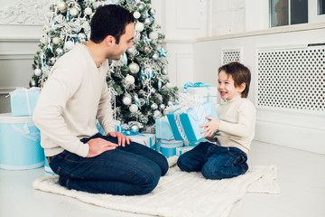 Father and son unwrapping a present lying on the floor