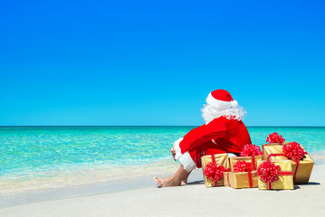 Christmas Santa Claus with gift boxes relaxing at ocean beach