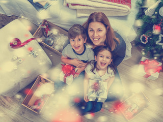 Mother with adorable children holding  holiday presents on christmas