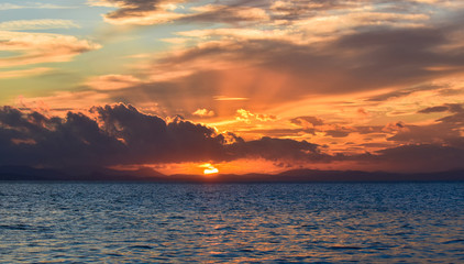 Sunset on the blue sea with clouds. The sun between clouds, .