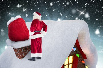 Santa claus standing on the roof top with his gift sack
