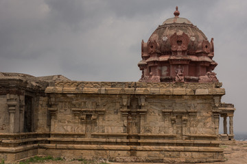 Dindigul, India - October 23, 2013: Wing with Vimanam at the abandoned ruinous Shiva Temple on the Rock in Dindigul. Red painted dome features statue of Dakshinamurthy Shiva  and Nandi. Gray sky.