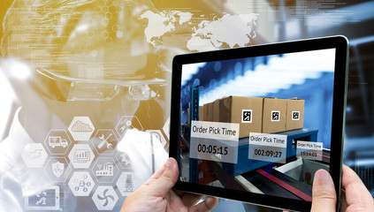 Industry 4.0,Augmented reality and smart logistic concept. Hand holding tablet with AR application for check order pick time in smart factory warehouse.Man use AR glasses and infographic background. Wall mural