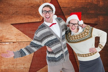 Happy couple in santa hat against digitally generated wooden bac