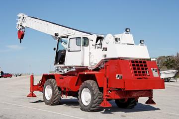 Heavy-duty hook on crane truck arm  against blue sky. Vertical.