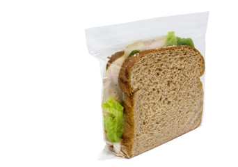 Basic turkey sandwich with lettuce on brown wheat bread in plastic baggie. Front and side view. Horizontal.