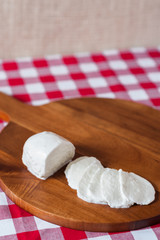 Water buffalo mozzarella mozzarella di buffala cheese in ball and sliced on wooden cheese chopping board on red and white checkered tablecloth with brown burlap background with copy space above