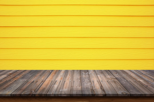 Wood table on yellow wood wall for background.