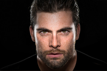 Handsome male model with masculine facial hair and intense eyes on isolated black background  Wall mural