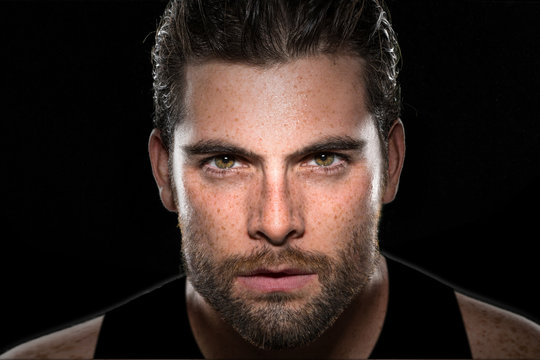 Handsome male athlete body builder with facial hair and intense eyes on isolated black background