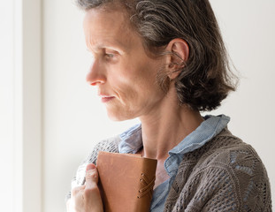 Profile view of middle aged woman with grey hair frowning and holding book (selective focus)