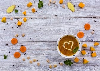 Creamy pumpkin soup with herbs and cream in the shape of hearts. Vegetarian food with space for text.