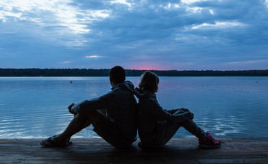 romantic couple enjoy morning sunrise on the lake. Sunset.