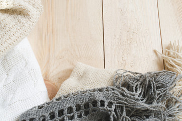 Cozy and soft winter background. Warm knitted clothes on a wooden background.