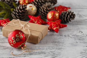 christmas gift with red balls bow on white wooden background