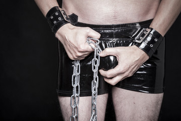 dominanter mann in latex shorts mit stahl kette
