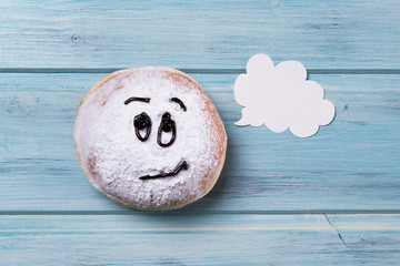 Donut with smiley face and text cloud, wooden background