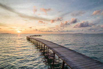 Pastel sunset behind a lonely wooden jetty