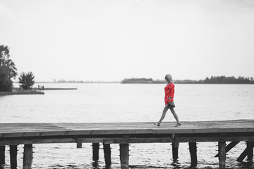 Woman in red jumpsuit at lake