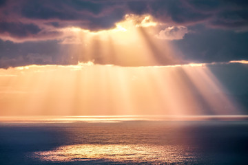 Rays of light after rain storm, seascape with sun reflections on water surface.