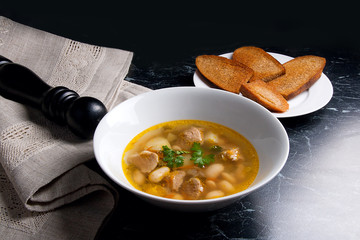 Bean soup in white plate, several toast on white plate on a blac