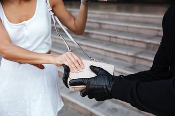 Criminal man in gloves stealing woman bag outdoors