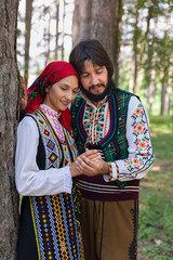Couple in Bulgarian traditional dress in a forest