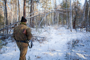 a hunter in the winter woods with a gun in camouflage clothing.