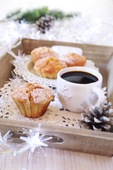 Christmas coffee break: muffins, cup of coffee and illuminated g