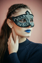Beautiful girl with black venetian mask