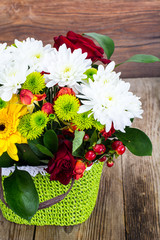 Floral arrangement of fresh flowers in the green wicker basket o