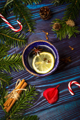 Christmas composition. Lemon tea with spices, Christmas tree, cinnamon sticks, cones, star anise and candy cane